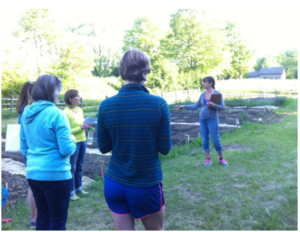 Caption: Community gardeners gather to hear from Master Gardener Bea Cole